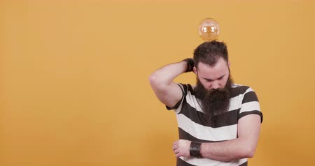 head over : Bearded young man with a bulb over his head getting an idea