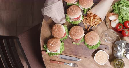 white onion : Top view composition with burgers and a chefs hands puts them on table. Many burgers, cheeseburgers on a wooden table. French fries, pickles, tomatoes and onions. Stock Footage