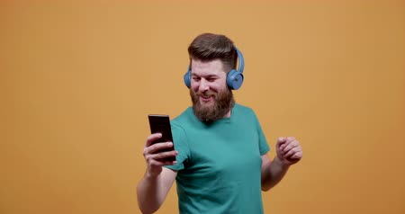 bigode : Handsome young man listens to music at his smartphone and dances. Joyfull man dancing and having fun listening to his favorite track.
