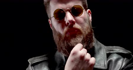 mastigação : Serious man with heavy metal look chews tabacco and touches his beard