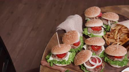 savanyúság : Dynamic reavealing shot of fast food on a wooden table. Burgers with lettuce, tomatoe and onion. A glass of beer, pickles and sauce.