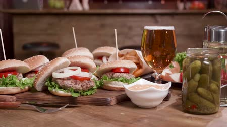 savanyúság : Many burgers, a bottle of pickles and a glass of blonde beer. Appetizing burgers on a wooden surface. From above to ground level. Stock mozgókép