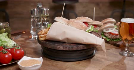 чизбургер : Delicious composition of fast food rotating on wooden board. Fresh white buns with homemade meat and french fries.