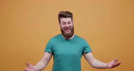 bigode : Portrait of a young hipster with big beard laughing very loud. Man on yellow background having lots of fun. Vídeos