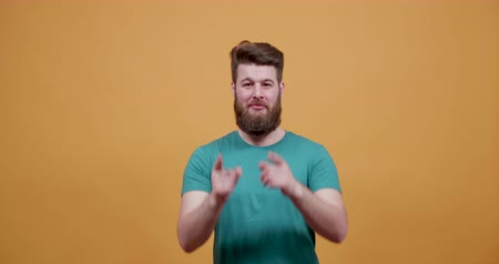 bigode : Young bearded man pointing his fingers in different directions. Point a direction in front of an yellow background. Subscribe. Look here. Vídeos