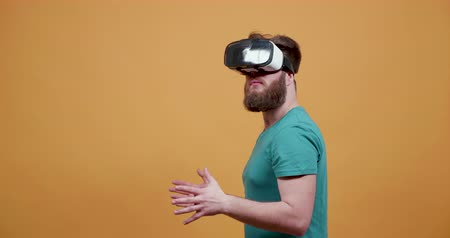 bigode : Man playing a strategy game on his virtual reality headset. Young man with beard playing games on vr set.
