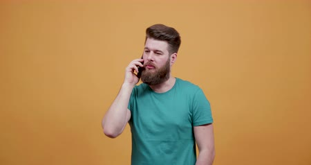 bigode : Attractive young man with nice beard engaged in a phone conversation. Man talks on the phone in front of a yellow background.