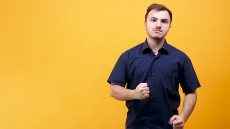 versão : Angry caucasian young man wants to fight somebody aggressively isolated on yellow orange background. 4K version is available here: https:videohive.netitemangry-caucasian-young-man-wants-to-fight-somebody23269718