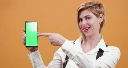 büszke : Woman pointing her finger to a smartphone with green screen on