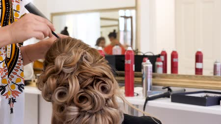 curling hair : Hairdresser working on a client hair