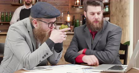 çözme : Two freelancers looking at the laptop screen and comparing the data. Stylish bearded men over a business meeting in a vintage style restaurant.
