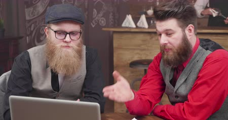 неформальный : Two guys in a vintage style coffee shop greeting their colleagues in an online video call