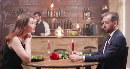słoneczko : Attractive young man and woman at a dinner. Couple enjoying themselves in a small vintage style restaurant.