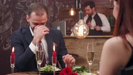 proposta : Young man being shy and emotional during a date. Very unconfident young man at a romantic dinner. Laughing and trying to be serious.