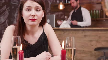 freio : Portrait of a young girl with sad eyes after a break up. Young caucasian girl looks unhappy at a dinner table in a restaurant.