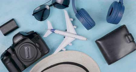 кошелек : Travel and holiday objects on a colored background slowly spinning. Traveler attributes for a perfect holiday trip. Camera, battery, hat, sunglasses, wallet.