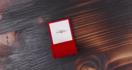 karát : Engagement ring in red case on vintage wooden background. Diamond ring in small red box.