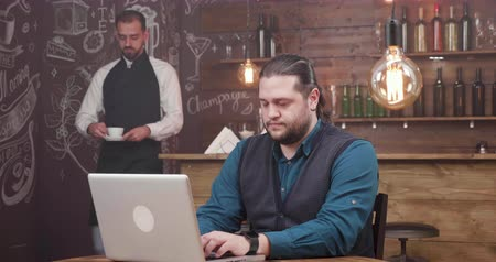 remotely : Man with long hair and beard works remotely and is getting a fresh coffee. Waiter bringing a coffee to a freelancer customer. Smiling and enjoying his work.