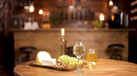 fresh cheeses : Beautiful composition of cheeses served with wine on wooden table. Smooth blured background of a restaurant interior.
