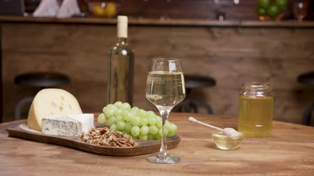 комбинированный : A bottle and a glass of wine combined with cheeses. Composition of cheese, walnuts and honey in a vintage restaurant.