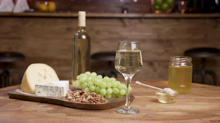 пармезан : Smooth slider shot of a cheese composition on wooden table. Food tasting with wine, honey and grapes. Wooden table.