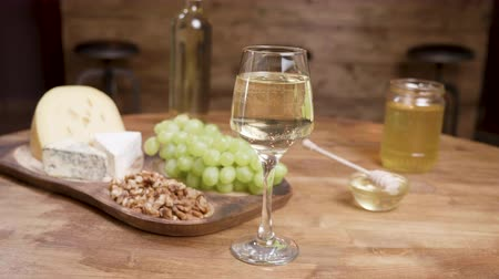 fresh cheeses : Cheese appetizers on a wooden table with wine and grapes. Glass of white wine and cheeses on a wooden tray.