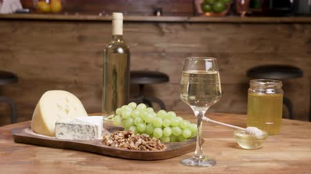 cheddar : Sliding towards a composition of different cheeses. Cheese appetizer on a wooden table with a glass of white wine.