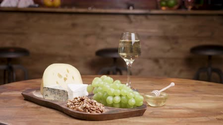 fresh cheeses : Artistic food composition of cheeses, grapes and wine. Appetizer on wooden tray in a vintage style restaurant.