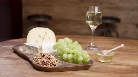 cheese piece : Cheese and grapes on a wooden table with honey, walnuts and wine. Food concept. Wine and cheese for tasting.