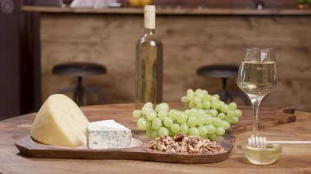 cheddar : Different sorts of cheese arranged on wooden table in a restaurant. Grapes, wine and honey for tasting purposes. Food art.