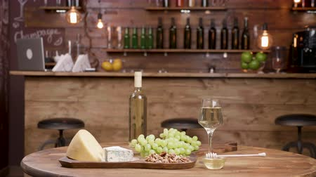 şarap kadehi : Paralax shot of a variety of cheeses served with white wine. Luxury winery concept. Wine and grapes.