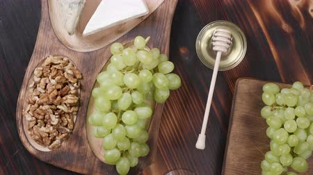 pieces of cheese : Top view of a food composition with cheese and wine. Rotating food on a wooden table. White grapes, brie, gouda and roquefort cheese.