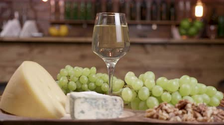 servido : A glass of white wine with grapes and a variety of cheeses. Collection of cheese on a wooden tray served with wine and grapes.