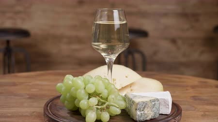 şarap kadehi : A beautiful glass of wine served with grapes a cheeses. Parralax shot of a cheese art composition. Wine and appetizer concept. Stok Video