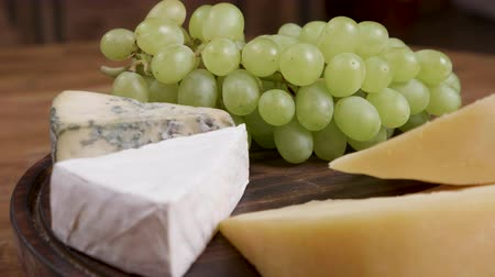 dorblu : Gouda, brie and dorblu cheese served with white grapes. Variety of cheeses on a wooden tray and wooden background. Stock Footage