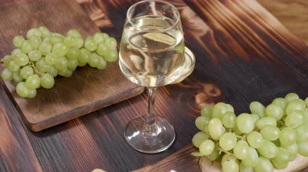 cheese piece : A glass of white wine shot from above on a wooden background Stock Footage