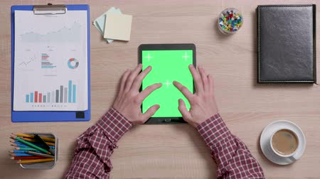 vertical : Top view of male using both hands to zoom in a green screen on a black tablet. Tracking motion. Office wooden desk. Corporate concept. Chroma key.