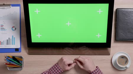 portable information device : Top view of mans hands scrolling over the left edge of a green screen touch monitor. Office and corporate concept. Big chroma key. Stock Footage