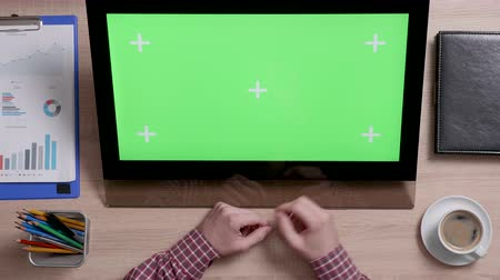portable information device : Top view of mans hands scrolling over the bottom edge of a green screen touch monitor. Office environment concept. Working indoors with coffee on the side.