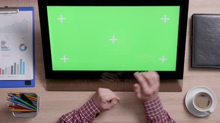 narożnik : Top view of a mans hands touch the bottom right corner of a green screen on touch monitor. Above shot of work environment concept. Chroma key. Business and finance.