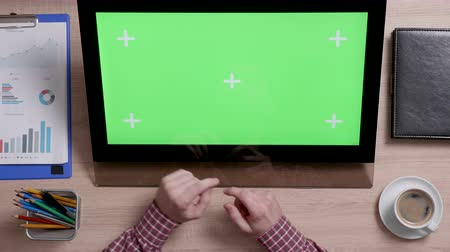narożnik : Top view of a mans hands touch the bottom left corner of a green screen on touch monitor. Above shot of work environment concept. Chroma key. Business and finance. Wideo