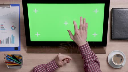 portátil : Top view of male fingers zooming in and out a green screen monitor. Office and corporate concept. Big chroma key.