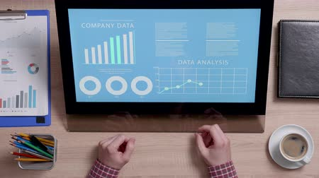 portable information device : Shot from above of a man looking at a monitor with company data graphs. Company financial report. Corporate concept.