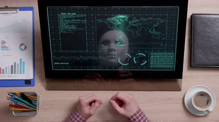 vista de cima : An incognito man with mask sits in front of a monitor with intelligence data on. Top secret information used by hacker. Stock Footage