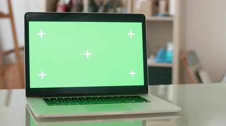 страница : Laptop with green screen on a glass office desk. Designers workshop concept. Chroma key.