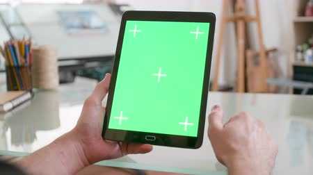 conserva : Man holds a black tablet with green screen on in both hands and keeps watching. Designer looking at sketches in his studio. Chroma key close-up shot.