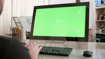 artsy : Man typing a text on his keyboard with a green screen on his monitor. Young designer working on his computer. Writing email in a artistic workshop environment. Stock Footage