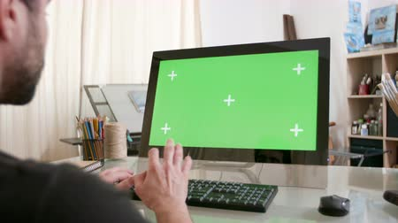 artsy : Young artist working at his computer with green screen on the display. Creative artistic director writing emails. Stock Footage