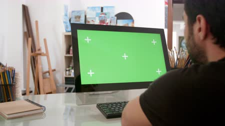 artsy : Bearded man looking at a green screen on his computer. Young painter, designer, looking at a green screen in a cozy workshop. Stock Footage