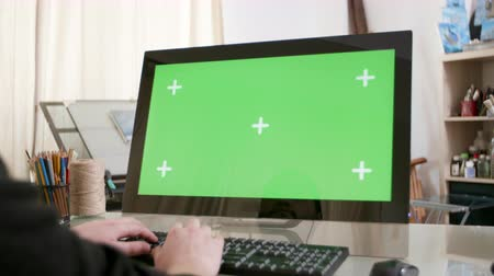 artsy : Male hands typing a text on a computer with green screen on. Artistic work environment. Creative job concept.